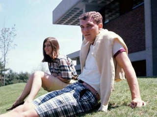 Paul Miller and date sitting on lawn near school building. Fall '66.